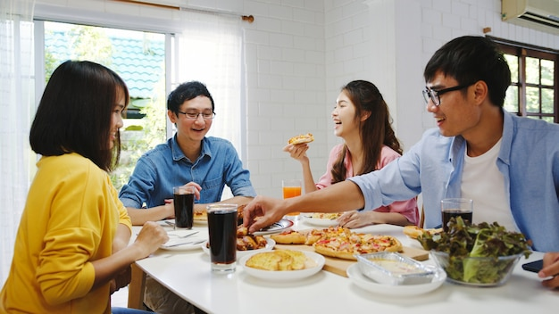 Happy young friends group having lunch at home. asia family party eating pizza food and laughing enjoying meal while sitting at dining table together at house. celebration holiday and togetherness.