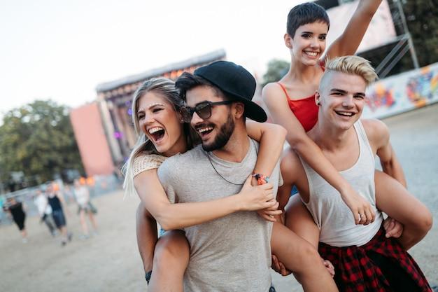 Счастливые молодые друзья веселятся на музыкальном фестивале