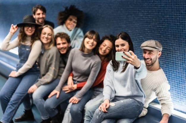 地下鉄の地下鉄駅で自分撮りを楽しんでいる幸せな若い友人-携帯電話を持っている手に焦点を当てる