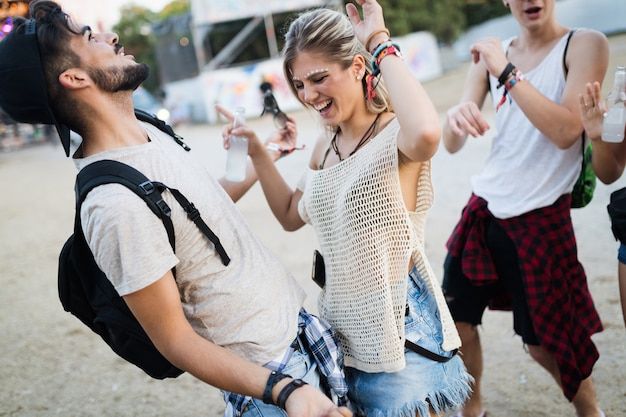 Happy young friends having fun at music festival