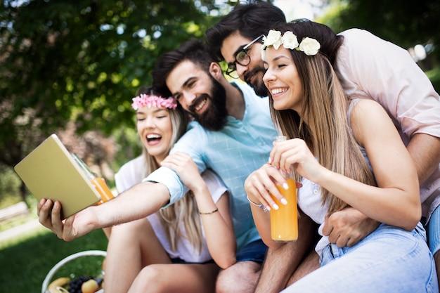 Счастливые молодые друзья в парке, пикник в солнечный день.