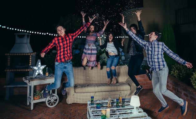 野外パーティーで色とりどりの紙吹雪の中でジャンプして腕を上げる幸せな若い友達