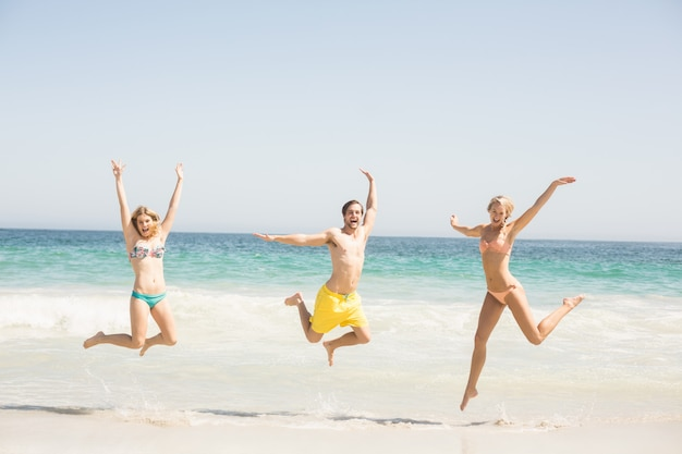 Happy young friends jumping on the beach