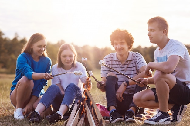 Happy young friends meet together, have party on nature, sit near bonfire, fry marshmallows, talk with each other, enjoy sunny warm summer day and calm atmosphere. teenagers and leisure concept