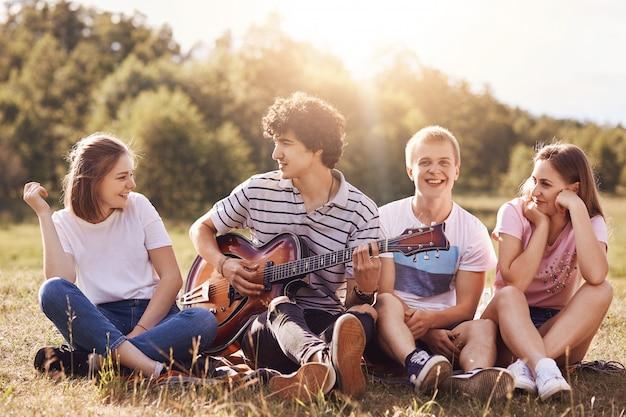 幸せな若い友達は、ギターに合わせて歌を歌い、一緒に喜び、屋外で再現し、緑の芝生に座っています。カーリーなハンサムな男性のティーンエイジャーはギターを弾き、彼の仲間をエンタナティンし、夏の暖かい日を楽しんでいます。