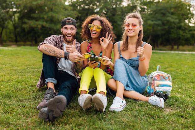 Счастливые молодые друзья сидят в парке с помощью смартфонов