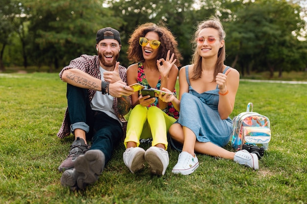 Happy young friends sitting at the park using smartphones