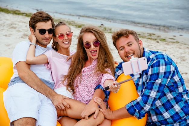 Happy young friends in sunglasses, resting together, taking a selfie on mobile phone