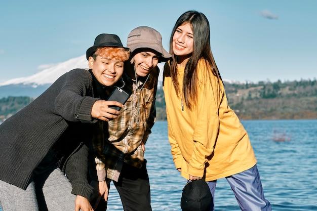 湖の近くの海岸線で携帯電話で自分撮りをしている幸せな若い友人