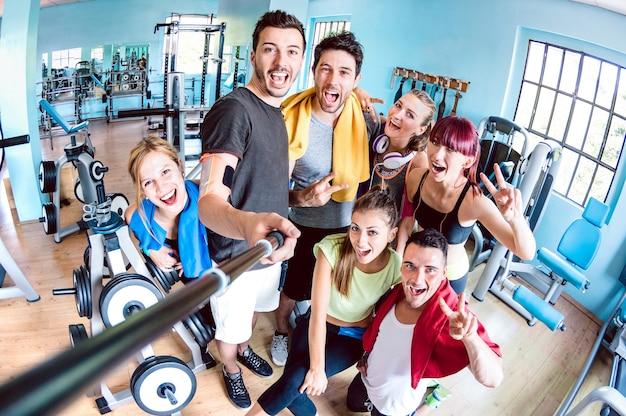 Счастливые молодые друзья, делающие селфи после открытия спортивного центра студии