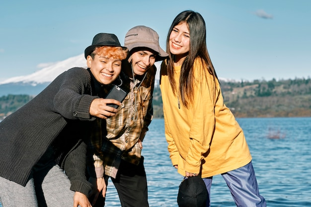Happy young friends taking a selfie with their cell phone in a coast line near a lake