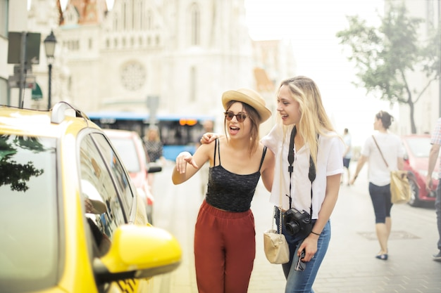 Happy young friends taking a taxi in summer