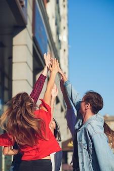행복 한 젊은 친구 팀워크. 함께 손으로 남자 amd 여자의 그룹은 하이 파이브 제스처를 제공