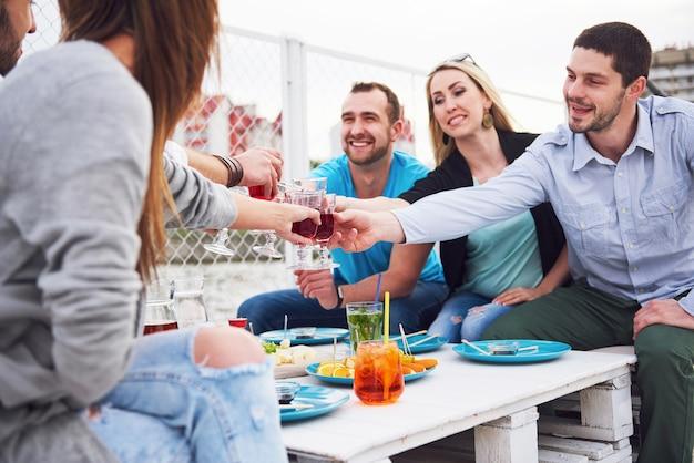 Счастливые молодые друзья сидели за столом и устраивали пикник на природе.