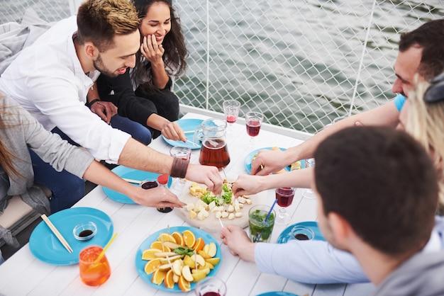 幸せな若い友人たちはテーブルに座って、屋外でピクニックをしていました。