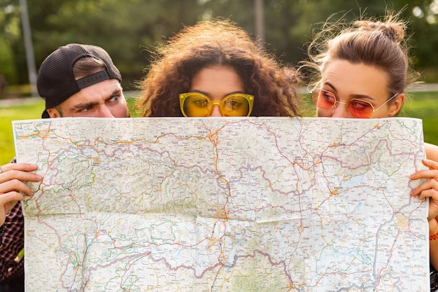 Happy young funny company of friends tourists hiding behind map in sunglasses, man and women having fun together, traveling
