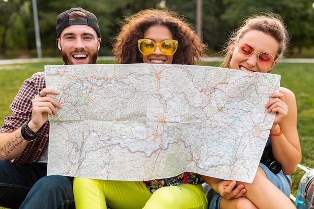 Felice giovane e divertente compagnia di amici turisti che si nascondono dietro la mappa in occhiali da sole, uomini e donne che si divertono insieme, viaggiando