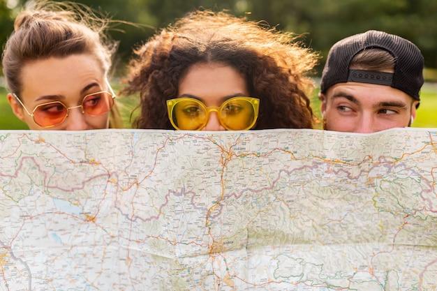 친구 관광객의 행복 젊은 재미 회사 선글라스, 남자와 여자가 함께 재미, 여행지도 뒤에 숨어