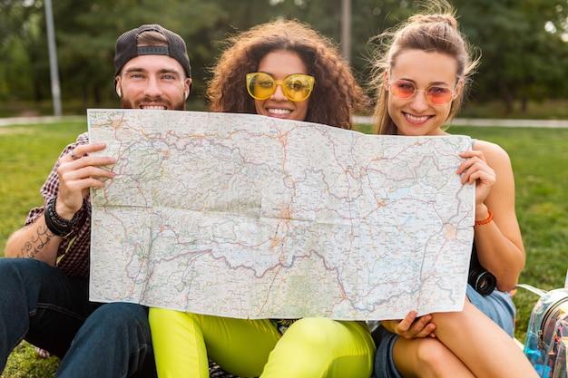 Счастливая молодая забавная компания друзей-туристов, прячущихся за картой в солнцезащитных очках, мужчины и женщины, весело проводящие время вместе, путешествуя