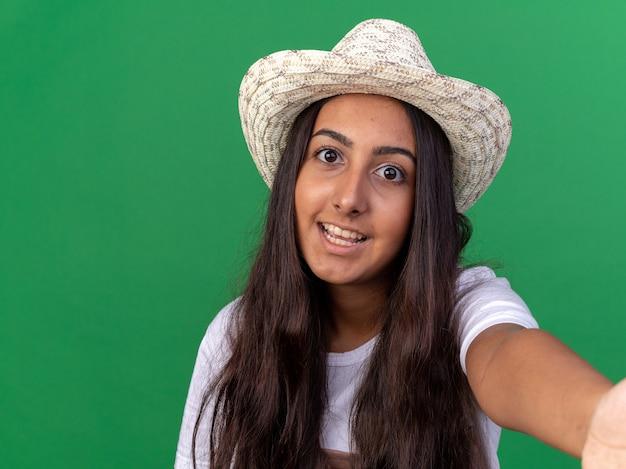 Felice giovane giardiniere ragazza in grembiule e cappello estivo felice e allegro sorridente in piedi sopra la parete verde