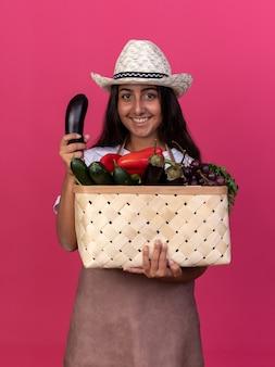 Felice giovane giardiniere ragazza in grembiule e cappello estivo tenendo la cassa piena di verdure e melanzane fresche con il sorriso sul viso in piedi sopra il muro rosa
