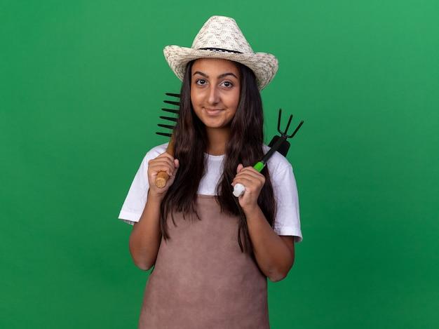 Felice giovane giardiniere ragazza in grembiule e cappello estivo azienda mini rastrello e mattock con il sorriso sul viso in piedi sopra la parete verde