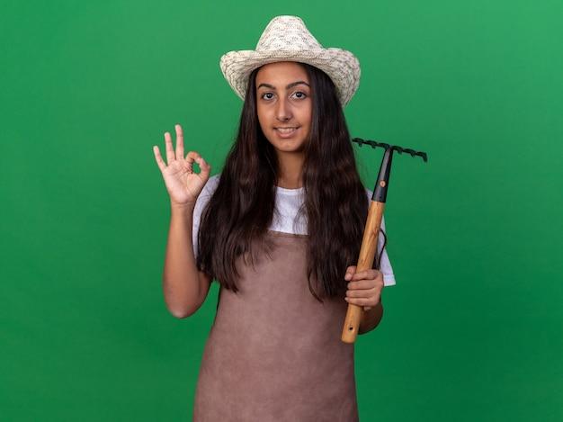 Felice giovane ragazza giardiniere in grembiule e cappello estivo che tiene mini rastrello che mostra segno giusto sorridente che mostra segno giusto in piedi sopra la parete verde