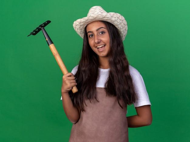 Felice giovane ragazza giardiniere in grembiule e cappello estivo che tiene mini rastrello con il sorriso sul viso in piedi sopra la parete verde