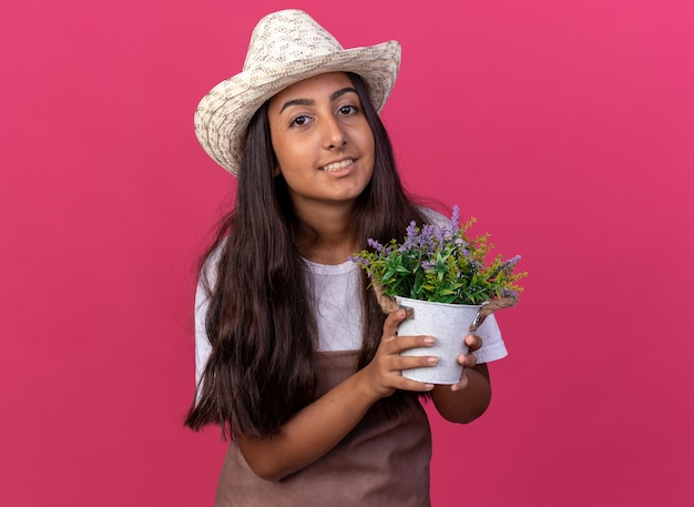 Happy young gardener girl in apron and summer hat holding potted plant  with smile on face standing over pink wall