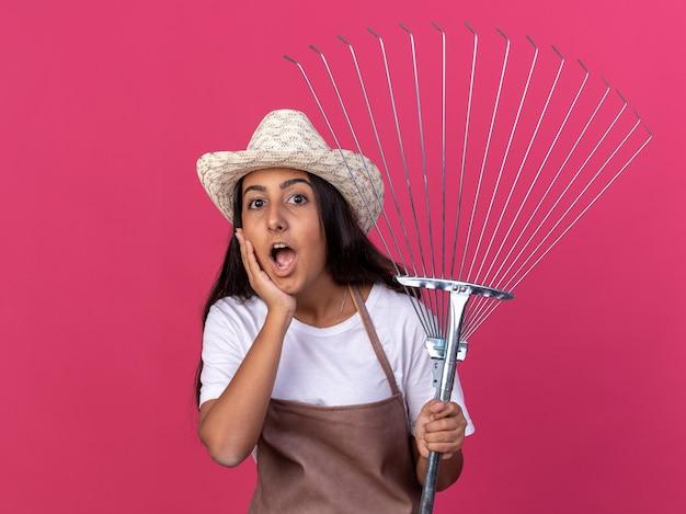Felice giovane giardiniere ragazza in grembiule e cappello estivo in possesso di rastrello stupito e sorpreso in piedi sopra il muro rosa