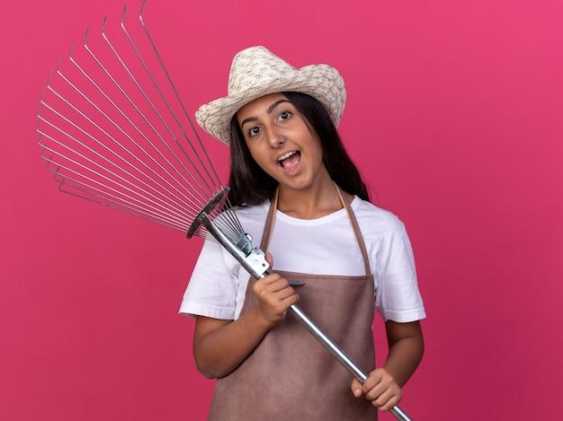 Felice giovane giardiniere ragazza in grembiule e cappello estivo tenendo il rastrello con il sorriso sul viso in piedi sopra il muro rosa