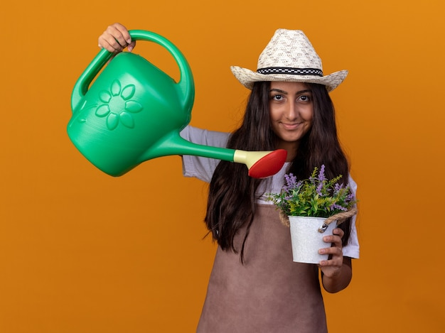 Happy young gardener girl in apron and summer hat holding watering can and potted plant watering plant with smile on face standing over orange wall