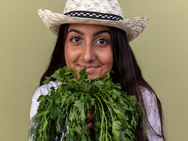緑の壁の上に立っている顔に笑顔で新鮮なハーブを保持しているエプロンと夏の帽子の幸せな若い庭師の女の子