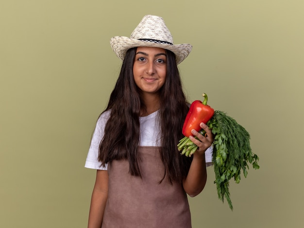 Счастливая молодая девушка-садовник в фартуке и летней шляпе держит свежий красный болгарский перец и свежие травы, улыбаясь, стоя над зеленой стеной