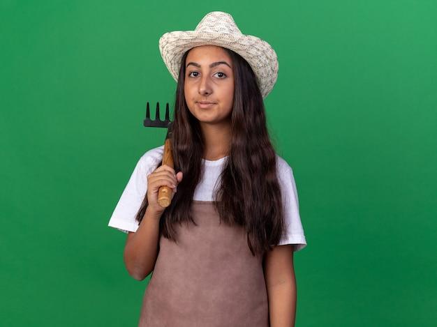 緑の壁の上に立っている顔に笑顔でミニ熊手を保持しているエプロンと夏の帽子の幸せな若い庭師の女の子