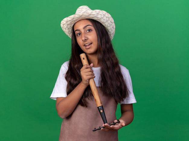 Счастливая молодая девушка-садовник в фартуке и летней шляпе держит мини-грабли с улыбкой на лице, стоя над зеленой стеной