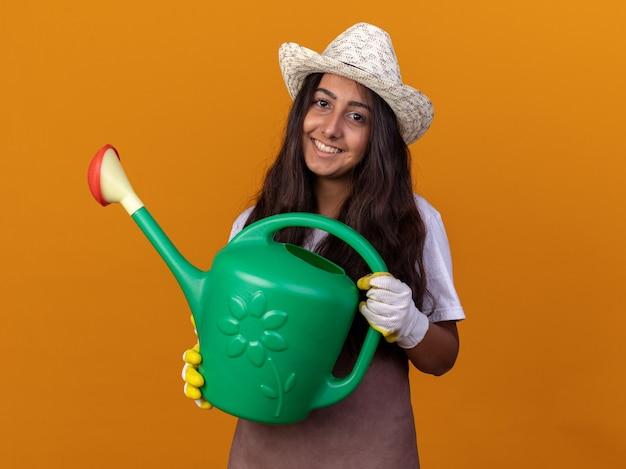 오렌지 벽 위에 서있는 얼굴에 미소로 앞치마와 물을 들고 여름 모자에 행복 젊은 정원사 소녀