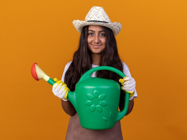 オレンジ色の壁の上に立っている顔に笑顔でじょうろを保持しているエプロンと夏の帽子の幸せな若い庭師の女の子