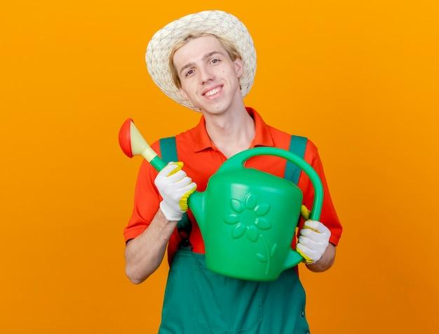 Felice giovane giardiniere uomo che indossa tuta e cappello tenendo annaffiatoio guardando la telecamera sorridendo allegramente in piedi su sfondo arancione
