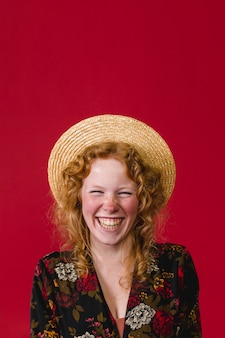 Happy young ginger woman wearing straw hat laughing