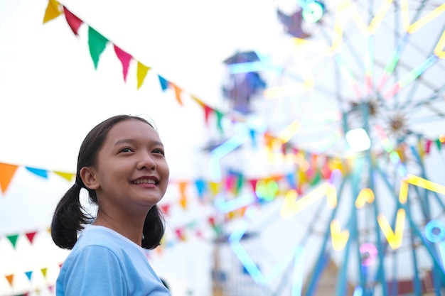 Happy young girl at the amusement park in night market.