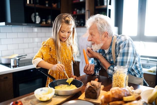 행복 한 어린 소녀와 그녀의 할아버지는 부엌에서 함께 요리