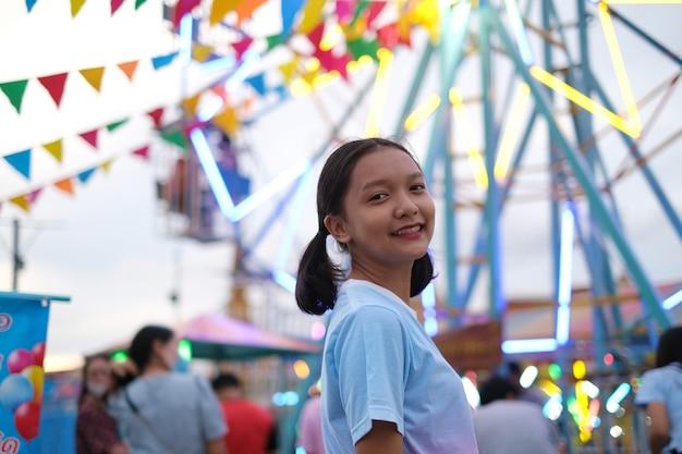 Счастливая маленькая девочка в парке развлечений на ночном рынке.