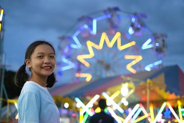 ナイトマーケットの遊園地で幸せな少女。