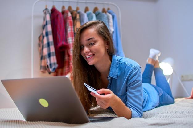 幸せな若い女の子のバイヤー買い物中毒のオンラインショッピングとクレジットカードとラップトップを使用して商品や購入の支払い。 eコマース