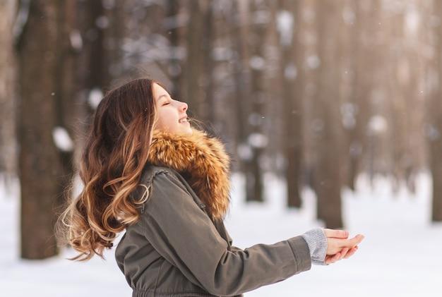 행복 한 어린 소녀는 화창한 날 야외에서 겨울에 눈송이를 잡는 다.