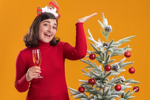 Felice giovane ragazza in maglione di natale indossando la fascia divertente tenendo un bicchiere di champagne sorridente allegramente con il braccio alzato in piedi accanto a un albero di natale oltre la parete arancione
