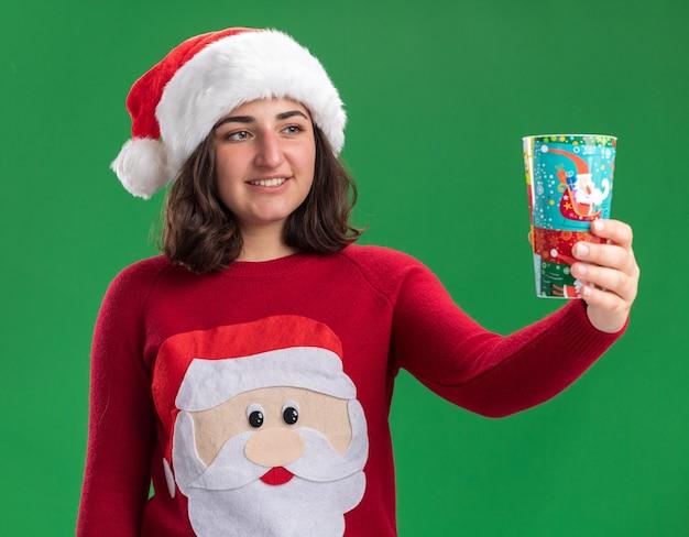 Giovane ragazza felice in maglione di natale che porta il cappello della santa che tiene il bicchiere di carta colorato guardandolo con il sorriso sul viso in piedi sopra la parete verde