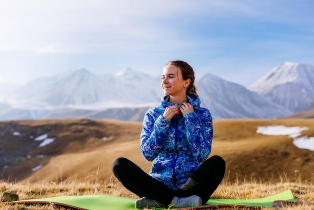 Счастливая молодая девушка, наслаждаясь природой и кавказскими горами