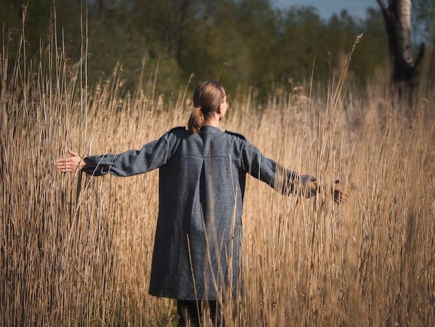 背の高い草で晴れた秋の日の美しさを楽しんで幸せな若い女の子